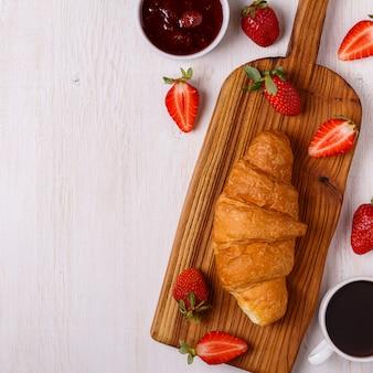 Śniadanie z rogalikiem, dżemem, owocami i kawą.