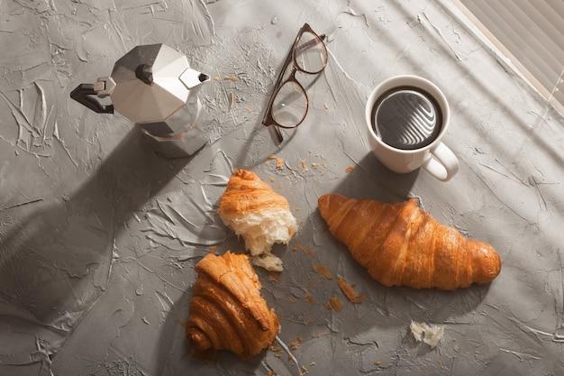 Śniadanie z rogalikiem na desce do krojenia i poranny posiłek z czarną kawą i koncepcja śniadania