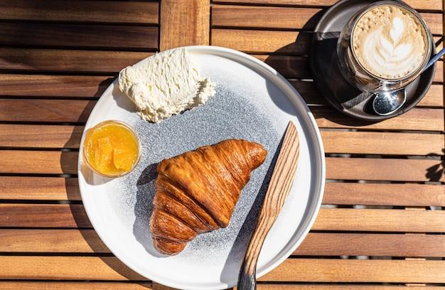 Śniadanie Z Rogalikiem Pomarańczowym I Masłem Z Cappuccino W Kawiarni Na świeżym Powietrzu W Słoneczny Poranek Premium Zdjęcia