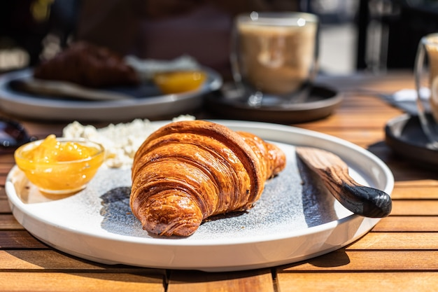 Śniadanie z rogalikiem pomarańczowym i masłem z cappuccino w kawiarni na świeżym powietrzu w słoneczny poranek