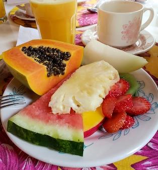 Śniadanie z różnymi owocami tropikalnymi. ananas, arbuz, truskawki, melon, papaja, mango, sok pomarańczowy.