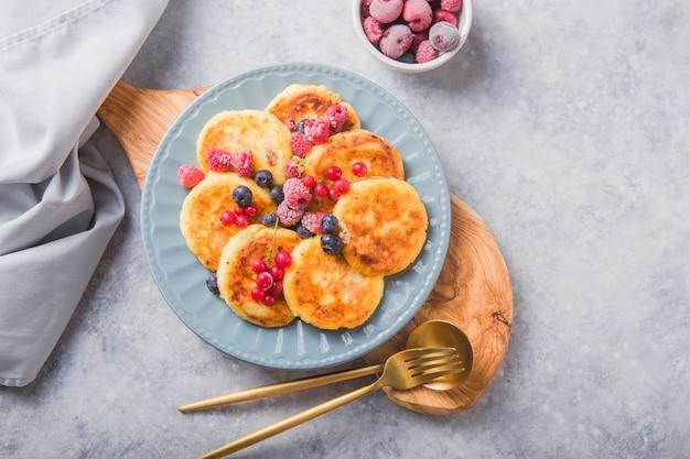 Śniadanie z sernikiem, świeże jagody. placki z twarogu lub twarogowe placki. rosyjskie syrniki lub sirniki