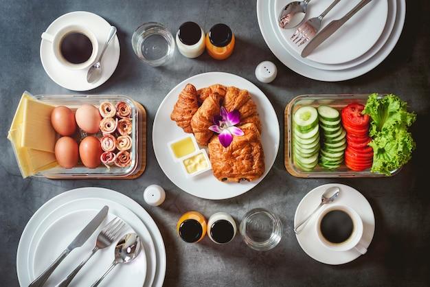 Śniadanie z szynką, jajkiem, ogórkiem, mlekiem, sokiem pomarańczowym, francuskim chlebem lub bagietką na czarnym tle