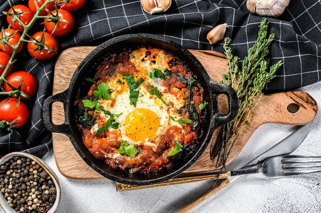 Śniadanie ze smażonymi jajkami i pomidorami shakshuka na patelni