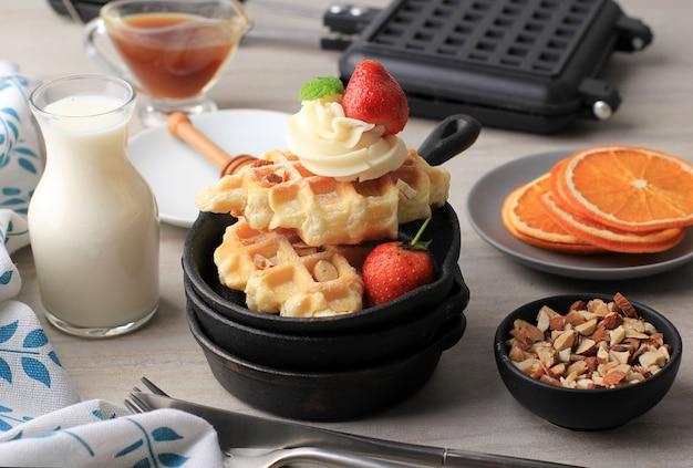 Śniadanie ze świeżo pieczonym pysznym domowym gofrem croissant z syropem klonowym, siekanymi migdałami i truskawką. podawane na mini żeliwie z mlekiem