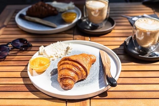 Śniadanie ze świeżym chrupiącym dżemem z rogalika pomarańczowego i masłem z cappuccino słoneczny poranek