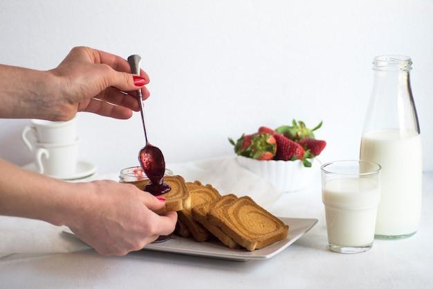 Śniadanie ze świeżym mlekiem, tostami, dżemem i truskawkami