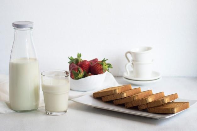 Śniadanie ze świeżym mlekiem, tostami i truskawkami