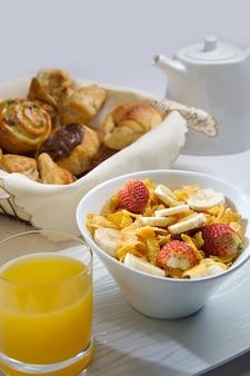 Śniadanie ze zbożami z owocami, sokiem i ciastkami.