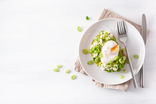 Śniadaniowa kanapka z awokado z jajkiem w koszulce i serem feta