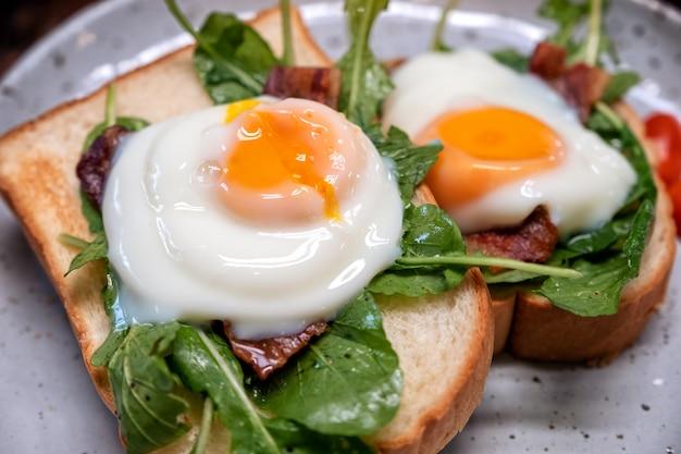 Śniadaniowa kanapka z jajkiem, bekonem i śmietaną w talerzu na drewnianym stole