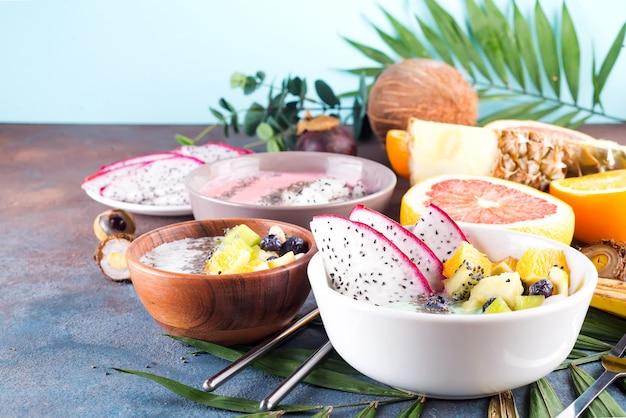 Śniadaniowa miska jogurtowa z pestkami pitaya, ananasem, chia i jagodami z liściem palmowym na tle kamienia, widok z góry