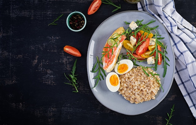 Śniadaniowa owsianka owsiana z gotowanym jajkiem, kanapką z łososiem i sałatką z pomidorów. zdrowe jedzenie. widok z góry, narzut, miejsce na kopię