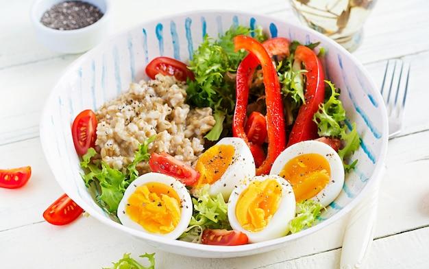 Śniadaniowa owsianka owsiana z zielonymi ziołami, gotowanym jajkiem, pomidorami i papryką. zdrowe, zbilansowane jedzenie.