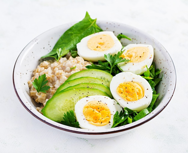 Śniadaniowa owsianka owsianka z gotowanymi jajkami, ogórkiem i zielonymi ziołami. zdrowa, zbilansowana żywność.