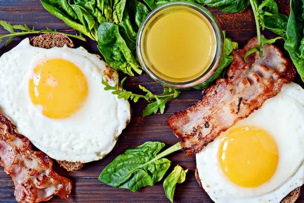 Śniadaniowe jajka sadzone z boczkiem, świeżym szpinakiem, rukolą i sokiem pomarańczowym.