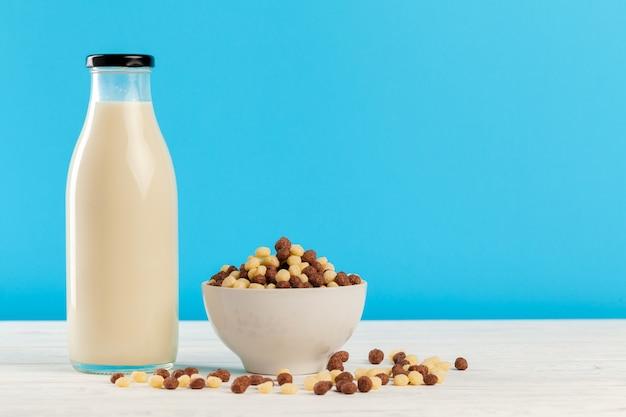 Śniadaniowe kulki zbożowe i mleko w szkle na niebieskim tle