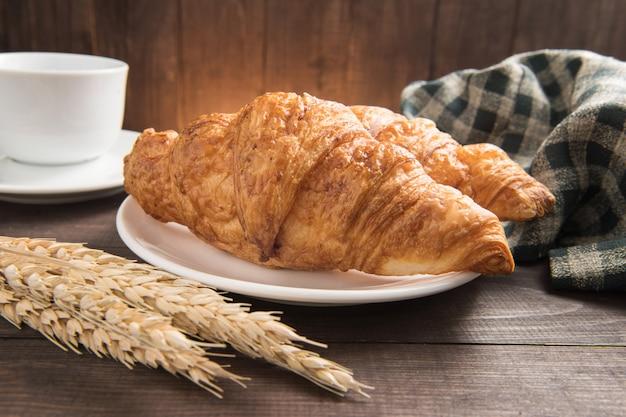 Śniadaniowy croissant i filiżanka na drewnianym tle