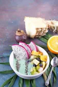 Śniadaniowy kiwi smoothie puchar nakrywający z pitaya, ananasem, chia ziarnami i jagodami z palmowym liściem na kamiennym tle, odgórny widok