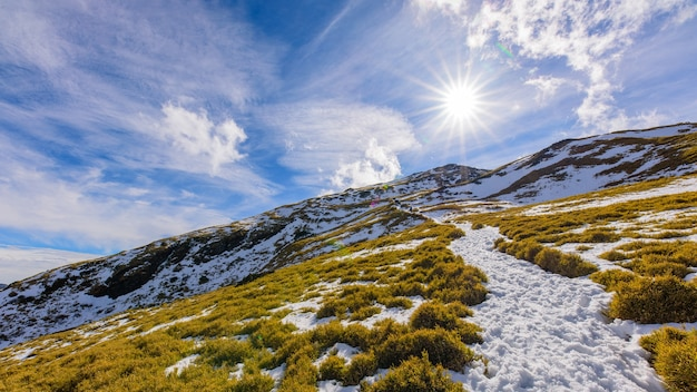 Śnieg, chmury, góry i słońce.