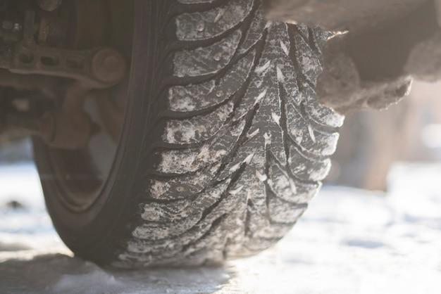 Śnieg i lód zimowe opony samochodowe zamykają koło pojazdu samochodowego