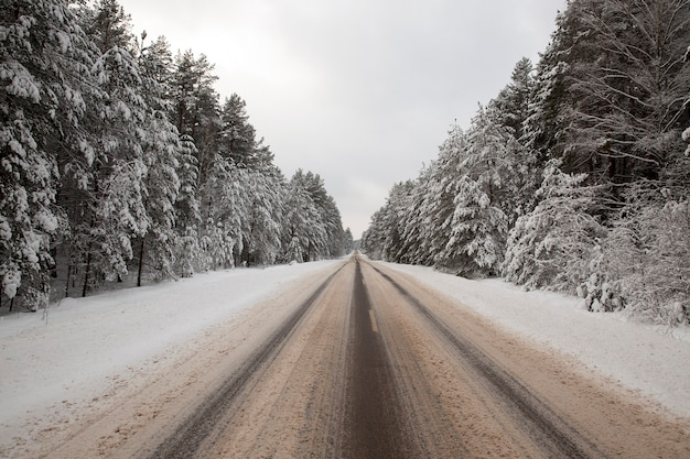 Śnieg na drodze. na powierzchni zostały wydrukowane ślady samochodów