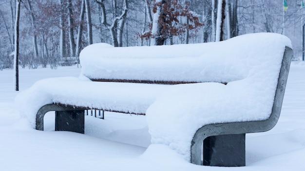 Śnieg na ławce w parku koncepcja zima