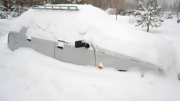 Śnieg na samochodach po opadach śniegu. samochód pod śniegiem po ciężkiej śnieżycy. zimowa scena miejska.