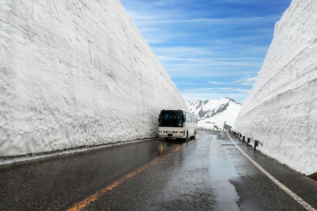 Śnieg ściana przy kurobe wysokogórskim w japonia z autobusem dla turystów na tateyama kurobe alpejskiej trasie