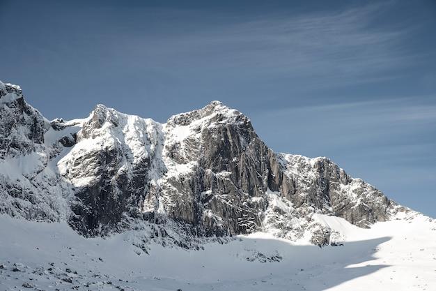 Śnieg skaliste pasmo górskie i błękitne niebo w zimie na lofotach, norwegia