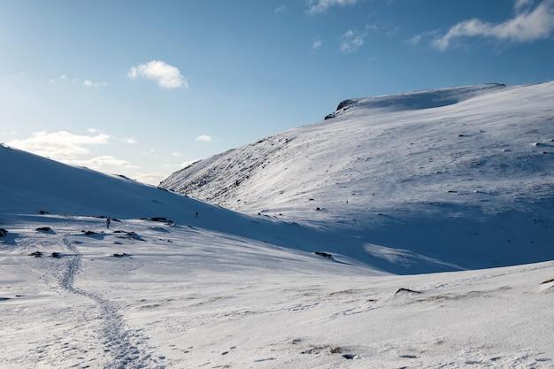 Śnieg stok wzgórza z błękitnym niebem na górze ryten na lofotach, norwegia