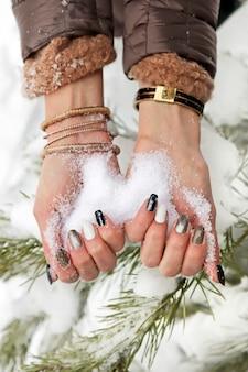 Śnieg w rękach dziewczyny z manicure