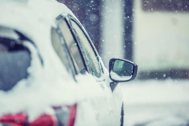 Śnieg wokół samochodu na drodze. sezon zimowy dla kierowców.