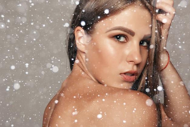 Śnieg, zima, boże narodzenie, ludzie, koncepcja piękna - beauty woman face portrait. ładna dziewczyna model spa z idealną świeżą czystą skórą na tle śniegu