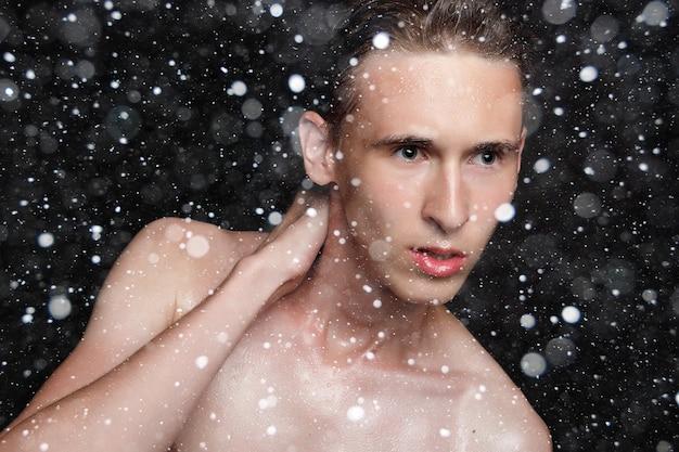 Śnieg, zima, boże narodzenie, ludzie, pielęgnacja skóry i koncepcja urody - mokry młody człowiek z czarnymi włosami na czarnym tle śniegu. portret mężczyzny z ogoloną klatką piersiową. pielęgnacja męskiej skóry. zgrany muskularny przystojny mężczyzna