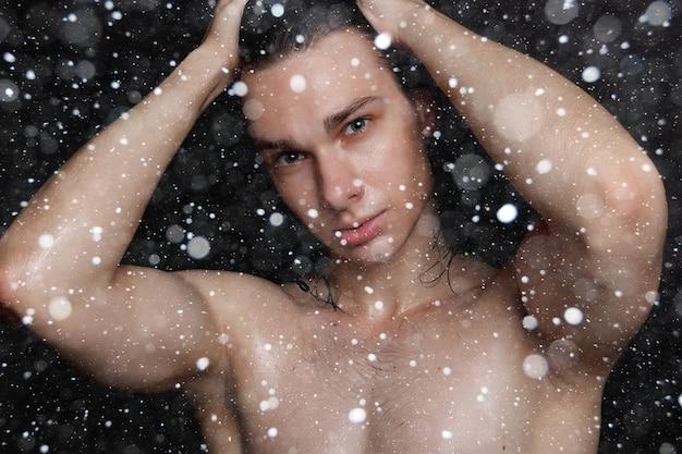 Śnieg, zima, boże narodzenie, ludzie, pielęgnacja skóry i koncepcja urody - mokry młody człowiek z długimi czarnymi włosami na czarnym tle śniegu. portret mężczyzny z ogoloną klatką piersiową. pielęgnacja męskiej skóry.