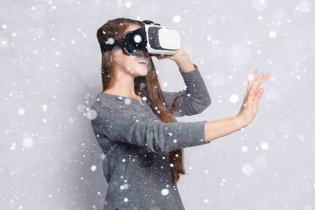 Śnieg, zima, boże narodzenie, technologia, rzeczywistość wirtualna, rozrywka i koncepcja ludzie - szczęśliwa kobieta zestaw słuchawkowy wirtualnej rzeczywistości lub okulary 3d. kobieta z goglami wirtualnej rzeczywistości na tle śniegu