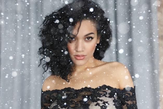 Śnieg, zima, święta, ludzie, koncepcja piękna - szczęśliwa, spokojna młoda kobieta z piękną oliwkową skórą i kręconymi włosami, idealną skórą i brązowymi oczami. zbliżenie portret na tle śniegu