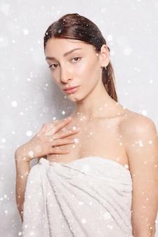 Śnieg, zima, święta, zdrowie, ludzie i uroda koncepcja - piękna kobieta w białym szlafroku po spa. zdjęcie zadbanej kobiety na tle śniegu. koncepcja odnowy biologicznej i spa.
