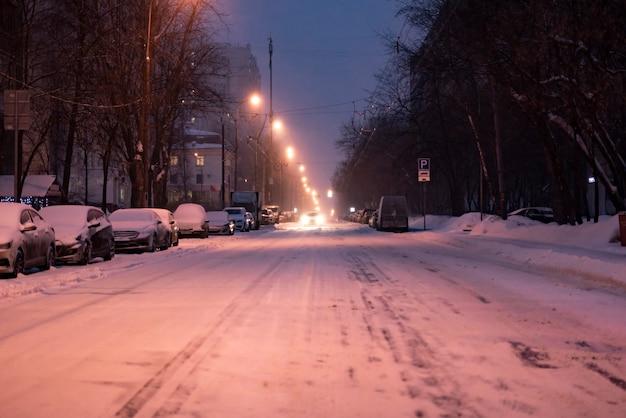 Śnieżna droga miejska z samochodami na uboczu w sezonie zimowym