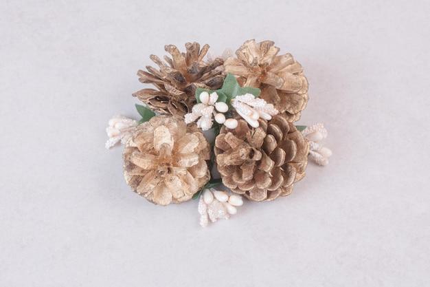 Śnieżna gałąź świerkowa z szyszek jodły na białym tle na białym stole.