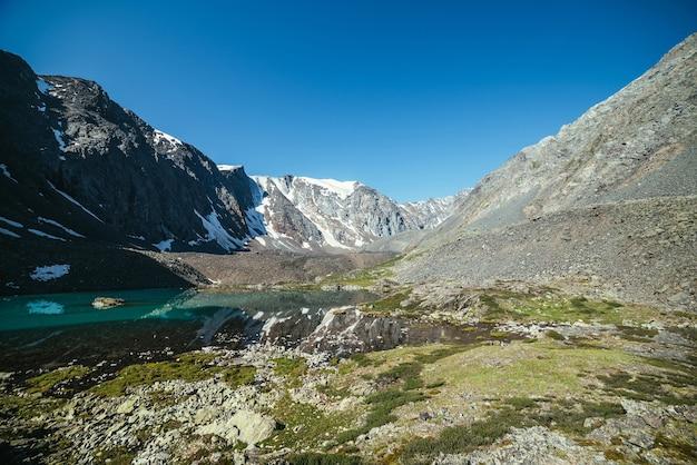 Śnieżna góra odzwierciedlenie w czystej wodzie jeziora polodowcowego. piękny słoneczny krajobraz z odbiciem lodowca w powierzchni wody jeziora górskiego pod bezchmurnym niebem. śnieg na skale odbity w górskim jeziorze.