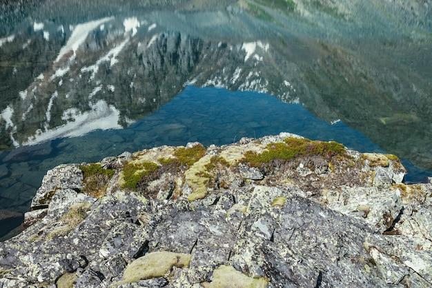 Śnieżna góra odzwierciedlenie w czystej wodzie jeziora polodowcowego. piękny słoneczny krajobraz ze śnieżnobiałym odbiciem lodowca w tafli wody jeziora górskiego. biały śnieg na skale odbity w górskim jeziorze.