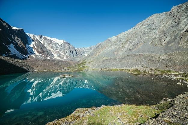 Śnieżna góra odzwierciedlenie w czystej wodzie jeziora polodowcowego.