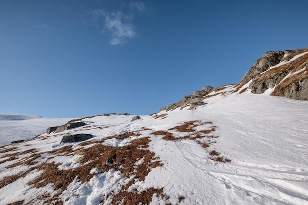Śnieżna góra ze skałami i błękitnym niebem w alpach na zimę