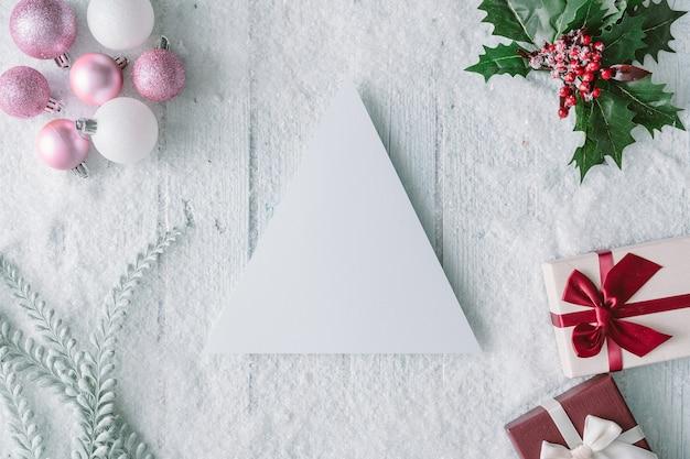 Śnieżna kompozycja świąteczna z kartką papieru i pudełkami na prezenty noworoczne. leżał na płasko. widok z góry.