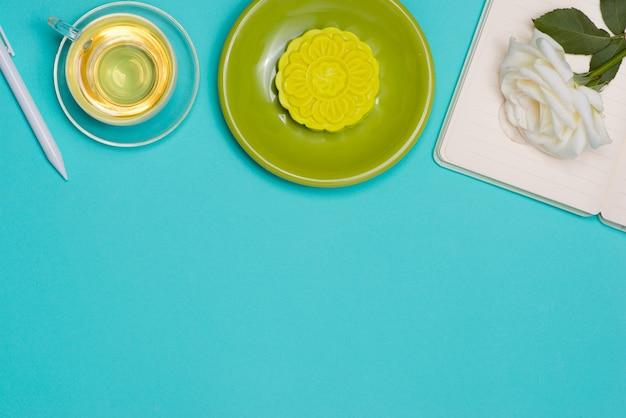 Śnieżna skóra mooncake i filiżanka herbaty z kwiatami. otwórz notatnik z miejscem na kopię.