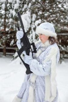 Śnieżna zima. młoda kobieta w śnieżnym dziewiczym stroju trzyma karabin.
