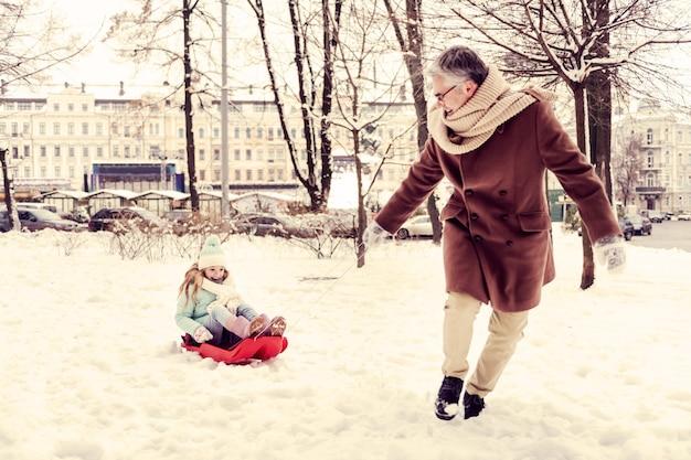 Śnieżna zima. urocza blondynka siedzi na sankach i uśmiech na twarzy