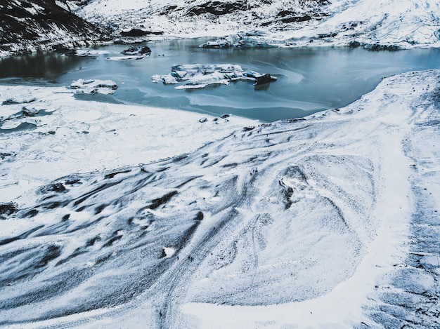 Śnieżne białe szlaki turystyczne w trudnych górach z zamarzniętym lodowatym jeziorem